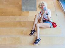 Fashionable beautiful young woman with long legs sitting on wooden stairs with a phone in her hand. Indoor Stock Photography