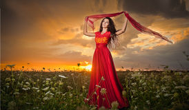 Fashionable beautiful young woman in long red dress posing outdoor with cloudy dramatic sky in background. Attractive brunette Royalty Free Stock Images