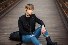 Fashionable beautiful young woman in a stylish black jacket. With jeans and boots sitting on the wooden floor royalty free stock photography
