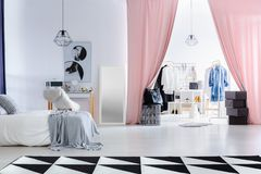 Fashionable bedroom with dressing room. Fashionable bedroom with poster above dressing table next to entrance to dressing room with clothes Royalty Free Stock Photos