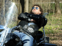 Fashionable biker relax sitting on his motorcycle Royalty Free Stock Photos