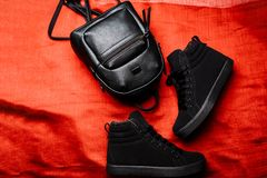 Black boots with a flat sole and black leather backpack on a red rag background stock photo