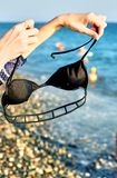 Black bra in the hands of a young girl on the beach. Fashionable black bra in the hands of a young girl on the beach Royalty Free Stock Images