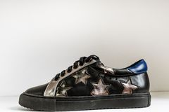 Black leather sneaker with a blue back and silver stars on a neutral background stock photo