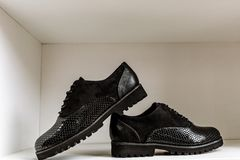 Black patent leather shoes with a snake-skin pattern against a white shelf in the store royalty free stock image