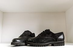 Black patent leather shoes with a snake-skin pattern against a white shelf in the store stock photo