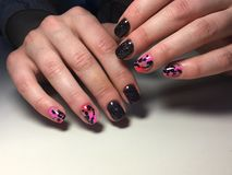 Fashionable black with pink manicure stock image