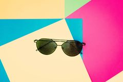 Fashionable black sunglasses on colorful paper backdrop. Texture background of fashion colors: pink, yellow, green, blue. royalty free stock images