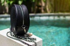 Fashionable Black woman bag. Close up of stylish female snakseskin python luxury bag outdoors. Fashionable and high royalty free stock photos