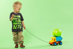 Fashionable blond cute boy pulling plastic car. Green bacground Royalty Free Stock Image