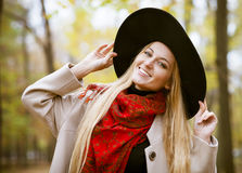 Fashionable blond woman at beautiful autumn alley Royalty Free Stock Image