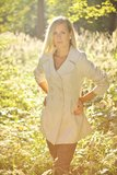 Fashionable blonde. Blonde in a coat posing in the grass Stock Photo