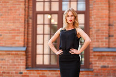 Fashionable blonde with arms akimbo against window of brick building. Fashionable blonde in black clothes, with arms akimbo against window of brick building Stock Photo