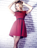 Fashionable blonde beauty in red dress. Royalty Free Stock Photos