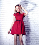 Fashionable blonde beauty in red dress. Royalty Free Stock Images