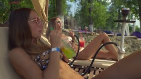 Fashionable blonde and brunette smoke a hookah and beat a cocktail at the beach stock footage