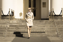 Fashionable blonde business lady in sun glasses walking Royalty Free Stock Photography