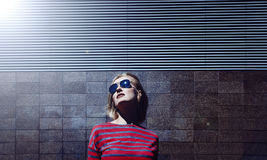 Fashionable blonde girl posing in sunglasses, on a metal striped background. Day, outdoor.Female dressed in striped pink t-shirt stock photo