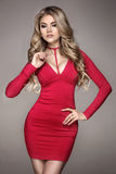 Fashionable blonde girl in red dress. Royalty Free Stock Photos