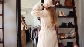 Fashionable blonde girl standing in front the mirror in beige coat and trendy hat, making a photo of look with her. Smartphone. Enjoying her style. Footage from stock footage