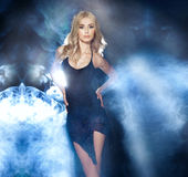 Fashionable blonde lady at the evening. Photo of beautiful blonde woman wearing elegant black dress , posing over the smoke. Long curly hair, looking at camera Royalty Free Stock Photos