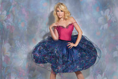 Fashionable blonde lady posing in floral skirt Royalty Free Stock Photos