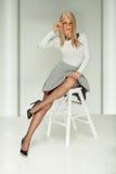 Fashionable blonde lady posing in studio. Beautiful fashionable blonde woman posing in studio, looking at camera stock image