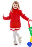 Fashionable blonde little girl with a cart in the Stock Photo