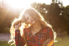 Fashionable blonde model in checkered dress posing in rays of sun royalty free stock images