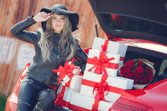 Fashionable blonde near the car with gift boxes Royalty Free Stock Photos