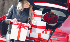 Fashionable blonde near the car with gift boxes Stock Photo