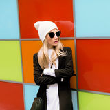 Fashionable blonde standing against a bright wall. Urban autumn Stock Image