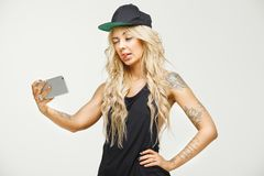 Image of female fashionable blonde in tattoos makes a selfie on white isolated. horizontal portrait of swag woman takes. Fashionable blonde in tattoos makes a Royalty Free Stock Photos