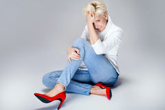 Fashionable blonde woman. Fashionable blonde adult woman posing in studio, wearing jeans and red high heels. Short hairstyle Stock Photography