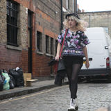 Fashionable blonde woman in in multi-colored blouse, black tights, shorts and a purple hat is on Columbia Road. Street fashion Royalty Free Stock Photo