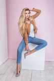 Fashionable blonde woman on pink background. Fashionable blonde beautiful woman with long hair posing on pink pastel background Royalty Free Stock Photography
