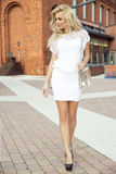 Fashionable blonde woman posing. Elegant fashionable beautiful blonde woman posing outdoor in casual clothes. Girl with long curly hair royalty free stock photo