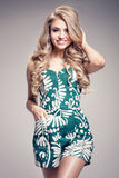 Fashionable blonde woman posing. Blonde fashionable woman posing in studio. Girl with long curly hair and glamour makeup. Fashion photo Stock Image