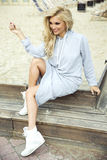 Fashionable blonde woman posing. Young fashionable beautiful blonde woman posing outdoor in casual clothes. Girl with long curly hair royalty free stock photos