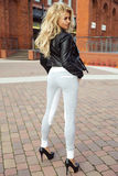 Fashionable blonde woman posing. Young fashionable beautiful blonde woman posing outdoor in casual clothes. Girl with long curly hair royalty free stock images