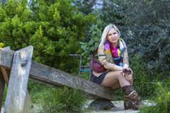 Fashionable blonde woman sitting in a Park on an old wooden swing. Royalty Free Stock Images