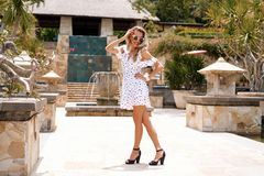 Fashionable woman wearing white dress and black heels. Fashionable blonde woman wearing white dress and black heels Royalty Free Stock Photography