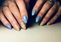 Fashionable blue manicure stylish yellow design drops splatter royalty free stock image