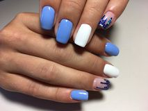fashionable blue manicure with white design and blue pawns stock photography