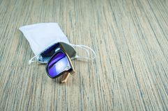 Fashionable blue sunglasses in a rag cover are wooden on the table stock image