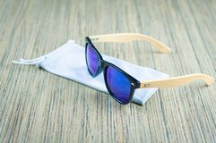 Fashionable blue sunglasses in a rag cover are wooden on the table royalty free stock photography
