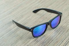 Fashionable blue sunglasses wooden on the table stock photo