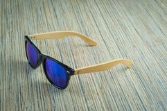 Fashionable blue sunglasses wooden on the table royalty free stock photography