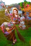 Fashionable in boho style girl holding broom Stock Photo