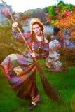 Fashionable in boho style girl holding broom Stock Photo